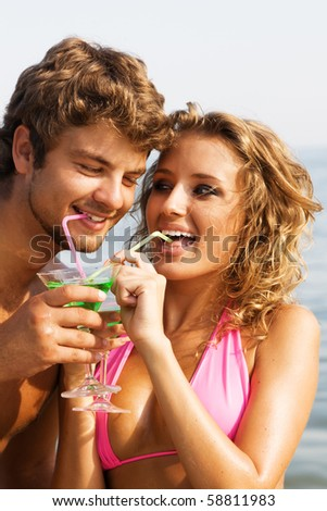 Young beautiful couple on the seaside drinking cocktails