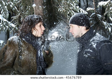 Young beautiful couple playing with snow in winter park. Girl blows some snow to her boufriend