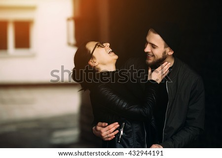 young beautiful couple posing in the side street at the camera - stock photo