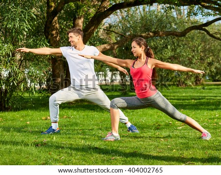 Young beautiful couple practicing stretching outdoors. Full-length.