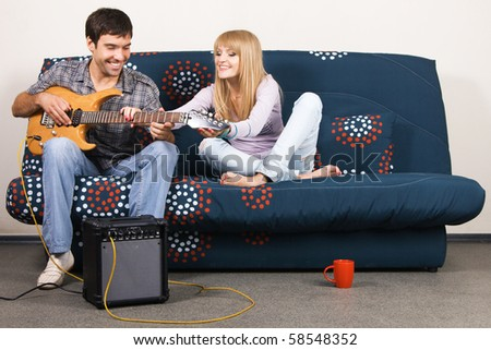 Young beautiful couple resting at home and playing electric guitar - stock photo