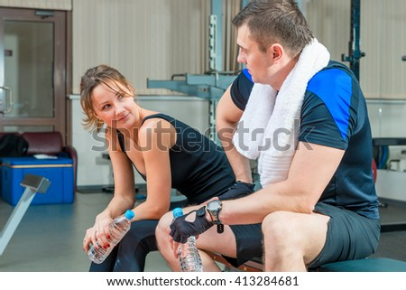 Young beautiful couple resting in a gym sitting on a bench after a workout - stock photo