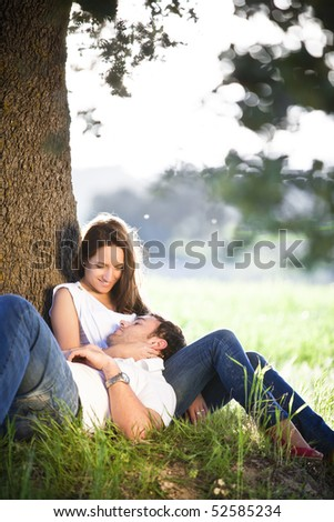 Young beautiful couple resting under a tree - stock photo