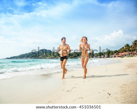 Young beautiful couple running on a tropical beach. Vacation, travel, honeymoon - stock photo