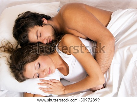 Young beautiful couple sleeping in bed - stock photo