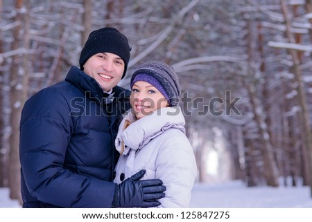 Young Beautiful Couple Smiling Outdoors in Snowy Winter - stock photo