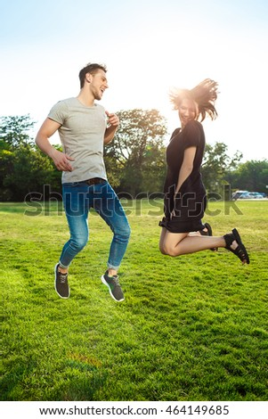 Young beautiful couple smiling, relaxing, jumping in park.