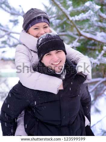 Young Beautiful Couple Taking Fun and Smiling Outdoors in Snowy Winter - stock photo
