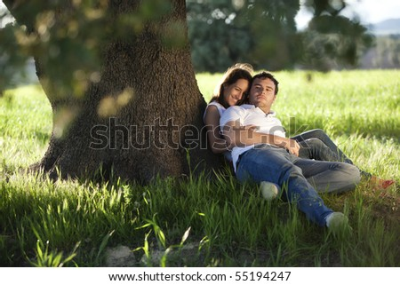 Young beautiful couple under tree. - stock photo