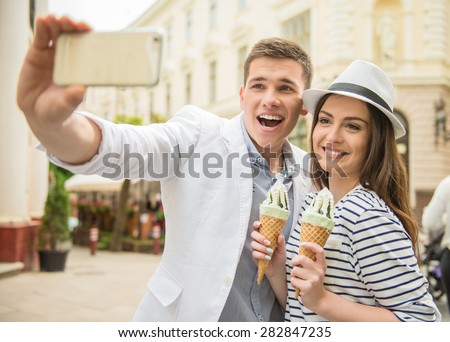 Young beautiful couple walking in the street and enjoying ice-cream. Romantic date. - stock photo