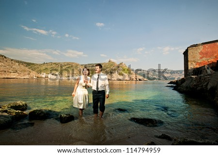 Young beautiful couple walking on water. Wedding in retro style. - stock photo