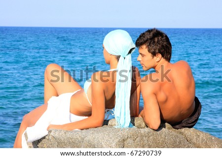 Young beautiful couple watching the sea - stock photo