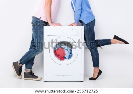 Young beautiful couple with a washing machine, on the white background. - stock photo