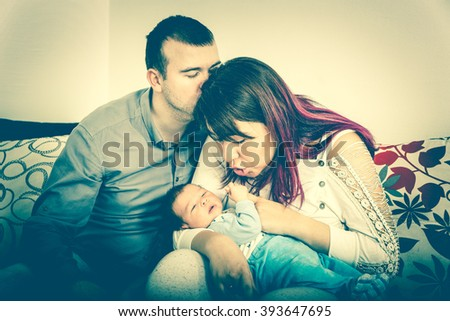 Young Beautiful Couple with New Baby at Home. Portrait of a Smiling Happy Family with the Kid in Bright Domestic Background. Man and Woman with Newborn Child Sitting. Carefree Moment of Happiness - stock photo
