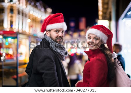 Young beautiful couple with Santa hats in the city - stock photo