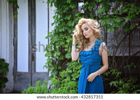 young beautiful curly blonde hair slim girl in blue dress holding bouquet of lupines looking away from camera dreaming in background old facade covered with wild grape. Healthy woman lifestyle concept - stock photo