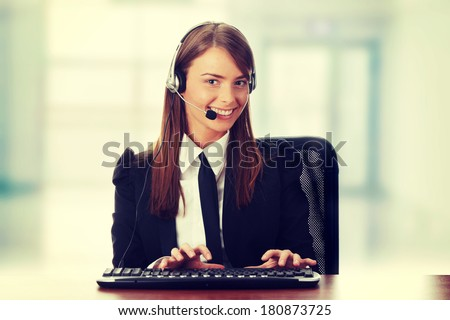 Young beautiful customer service operator girl in headset ,sitting at the desk  - stock photo