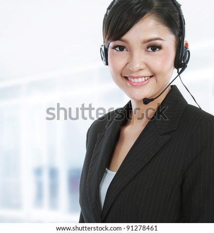 Young beautiful customer service operator with headset on her office - stock photo
