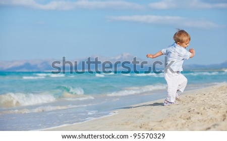 Young beautiful cute boy playing with wave at pretty beach. Majorca - stock photo