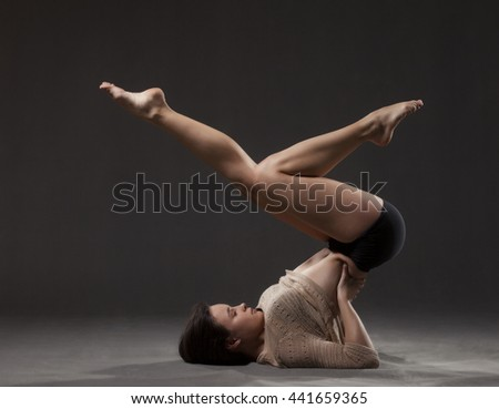 Young beautiful dancer in beige sweater and black leotard posing on a gray studio background - stock photo