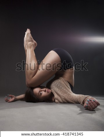 Young beautiful dancer in beige sweater and black short pants posing on a gray studio background