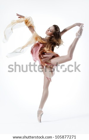young beautiful dancer posing on a studio background