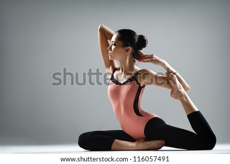 young beautiful dancer posing on a studio background - stock photo
