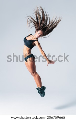 young beautiful dancer posing on studio black background - stock photo