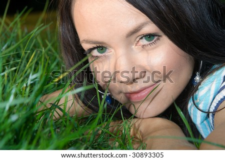 Young beautiful dark-haired woman lying at grass and smiling