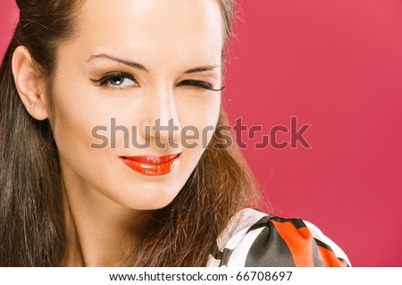 Young beautiful dark-haired woman winks and smiles, on red background.