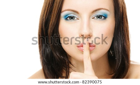 Young beautiful dark-haired woman with bared shoulders puts forefinger to lips as a sign of silence, isolated on white background. - stock photo