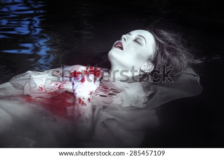 Young beautiful drowned woman in bloody dress lying in the water outdoor - stock photo