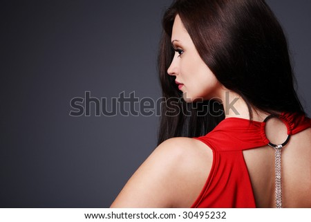 Young beautiful elegant brunette in red dress. - stock photo
