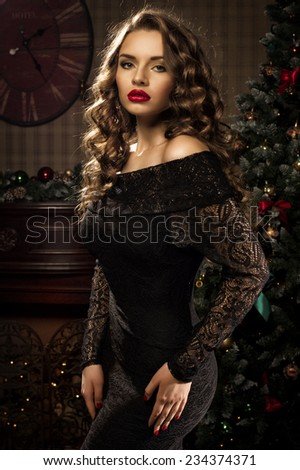 Young beautiful elegant lady in black evening sexy dress posing in christmas decorated interior. Fashion style portrait of young caucasian brunette woman in interior - stock photo