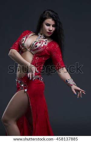 Young beautiful exotic eastern women in ethnic red dress on gray background. Studio shot - stock photo