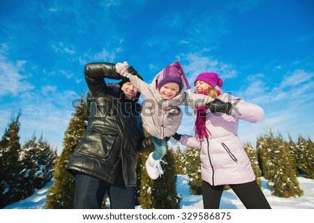 Young beautiful family in bright clothes winter fun jumping and running, snow, lifestyle, winter holidays