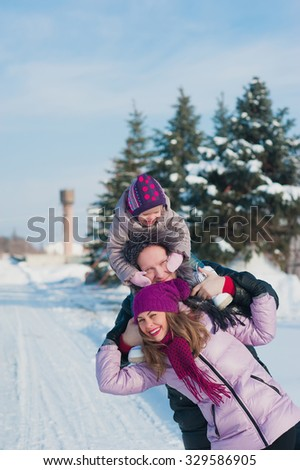 Young beautiful family in bright clothes winter fun jumping and running, snow, lifestyle, winter holidays - stock photo