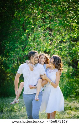 Young beautiful family of three having fun together outdoor. Pretty daughter on her father back. Parents and girl look happy and smile. Happiness and harmony lifestyle.