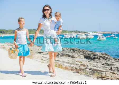 Young beautiful family of three walking along tropical beach - stock photo
