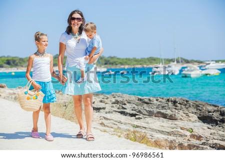Young beautiful family of three walking along tropical beach - stock photo