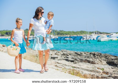 Young beautiful family of three walking along tropical beach
