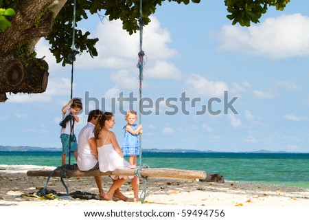 Young beautiful family swinging on tropical beach
