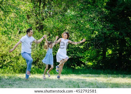 Young beautiful family three running playing in the park mother father daughter