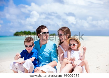 Young beautiful family with two kids sitting on tropical vacation - stock photo