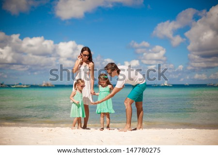 Young beautiful family with two kids walking at tropical beach - stock photo