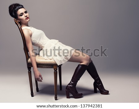 young beautiful fashion model sitting on a retro chair and looking at camera on gray background - stock photo