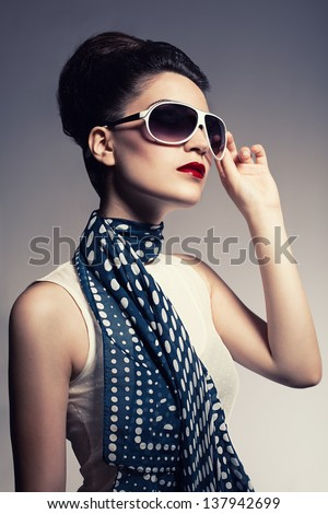 young beautiful fashion model with a spotted blue scarf posing on gray background - stock photo