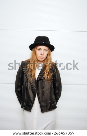 Young beautiful fashionable woman in hat, leather jacket and white blouse posing outdoors against garage door - stock photo