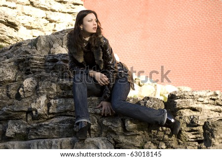 Young beautiful fashionable woman posing outdoor against old stone and brick wall at Kremlin Moscow Russia