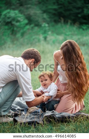 Young beautiful father, mother and little toddler son against green trees. Happy family with her baby boy on a summer sunny day. Family walking on the meadow.